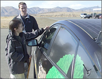 Photo of a man and a boy standing outside on a test track examining the roof of a car outfitted with scientific measuring equipment. In the background are mountains.