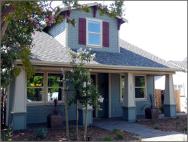 Photo of the front view of a new 1.5-story traditional bungalow painted gray with white trim and maroon red shutters. The front patio features four columns and a pathway made of brick pavers. The yard is landscaped with small plants and woodchips.