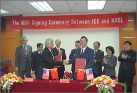 Photo of eight men and one woman gathered at a long table and applauding the signing of the agreement.  Pictured at front are two men who direct the collaborating scientific organizations. They are smiling and shaking hands. The table is decorated with flowers and small U.S. and Chinese flags.