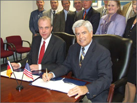 Photo of a close-up view of two men sitting at a table, holding pens and smiling after signing an agreement. Behind them are several men and women who work for the programs.