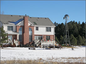 Photo of a large two story home with the roof exposed to the sun. On the right of the home is a windmill.