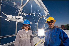 Photo of a young woman and a man with a moustache, both wearing hardhats and dark safety glasses, standing outside in front of a large curved metal reflector. The man is holding a small square-shaped sample of the silver reflective surface, which replaces heavy glass mirrors in the design. The large reflector is streaked with snow and frost after a recent winter storm.