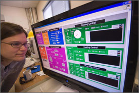 Photo of a young woman wearing a sweater and eyeglasses peering closely at a computer screen displaying data from eight different instruments analyzing the performance of a new parabolic trough that collects solar energy for use in making electricity.