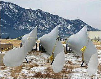 Photo of three wind turbine blades resting side by side on cradles with wooded, snowy mountains in the background.