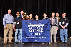 Photo of a line of people standing behind a sign that reads U.S. Department of Energy National Science Bowl Regional Winning Team 2009. One of the team is holding a trophy.