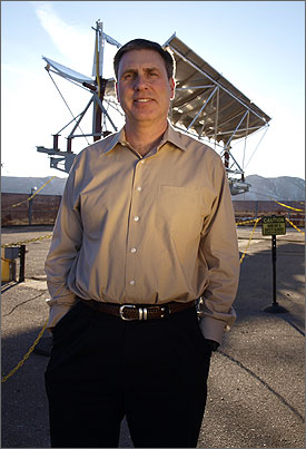 Photo of a man standing in front of large solar collector with mountains in the background.