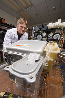 In a photo, a man with straight brown hair wearing safety glasses and a white lab coat leans over electronic components that were removed from a hybrid automobile engine. In the background is the car's radiator.