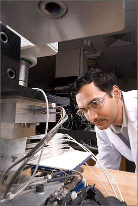 In a photo, a man with curly black hair and wearing safety glasses and a white lab coat watches liquids pass through clear tubes connected to laboratory testing equipment.