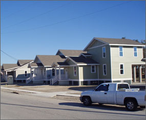 Photo of a view down the street of several small new homes being completed in New Orleans. The bare front yards have been graded, but are not landscaped. A white pickup truck is parked on the street in the foreground.