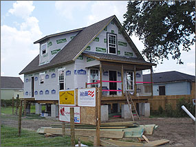 Photo of a small two story house under construction. It is built on elevated piers several feet high to avoid floodwaters. The front porch is being framed and is marked with bright pink warning tape.