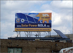 Photo of a billboard that reads 50% tax credit, www.SolarPowerNOLA.org, and New Orleans is a U.S. Department of Energy Solar America City. The blue and orange billboard has a photo of solar cells on it.