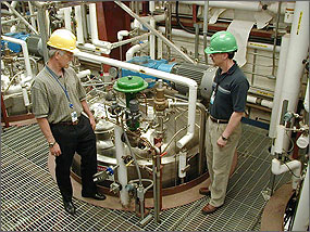 Photo of two men in hard hats looking at the gauges on top of a silver tank with pipes coming from it.