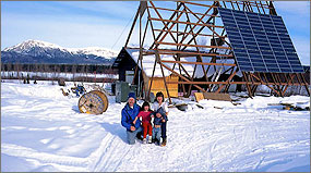 Photo of a native family of three in Alaska kneeling in the snow outside of their small wood frame home. The roof features a several photovoltaic panels installed at a steep angle.