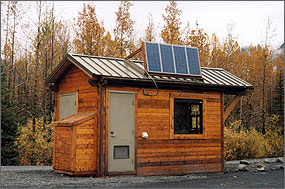 Photo of a small log cabin standing at the edge of the woods. The roof is made of sheet metal and features four photovoltaic panels standing up at a sharp angle