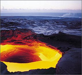 Photo of a doughnut-shaped vent near a volcano glowing yellow and dark red against a background of black rock.