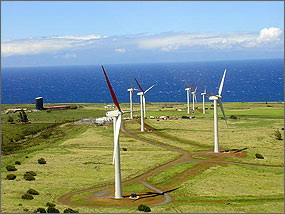 Photo of rows of white wind turbines standing in a green meadow with the blue ocean and white puffy clouds in the background.