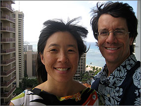 Photo of a woman and a man wearing tropical clothing smiling and standing on a balcony of a high-rise apartment building with the ocean visible in the background.