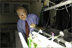 Photo of a man wearing safety glasses, business clothes and a necktie standing over a flask containing green liquid in a laboratory.