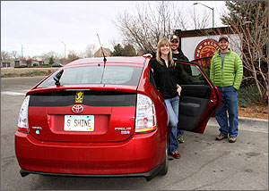 Photo of three people standing next to a red hybrid car.