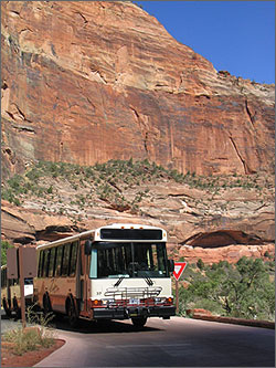Photo of a shuttle bus on a road in front of a large, red rock mountain side with trees and blue sky in the background.