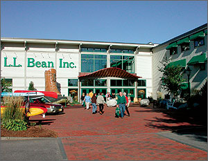 "Photo of retail building with a sign that says ""L.L. Bean"" in addition, there are people, kayaks and a large boot in front."