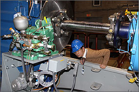 Photo of a man wearing a tan sweater, safety glasses and a hardhat ducking beneath machinery to inspect its wiring.