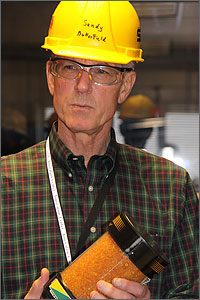 Photo of  a man wearing a yellow hard hat, safety glasses and a plaid shirt.