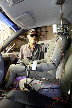 Photo of the inside of a car with bright lights shining through the windshield. A man wearing protective eye wear adjusts a human form made of metal and wires.