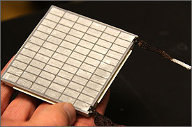 Photo of a man's hand holding a square metal object with a grid visible on the surface and connectors coming off the ends.