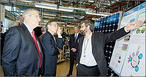 Photo of two men looking on as a scientist explains his photovoltaics research using a large poster with scientific diagrams.