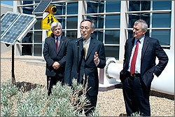 Photo of a man dressed in a business suit standing at a microphone answering news media questions flanked by two other men. They are standing near a dark blue photovoltaic panel and a section of a white wind turbine blade.
