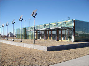 Photo of a modern looking rectangular-shaped building with glass walls. Three small white wind turbines are visible over the roof of the building.