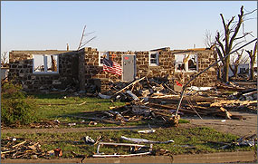 Photo of a heavily damaged, roofless brick home is surrounded by tornado debris. An American flag flutters from the home's front steps.