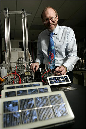 Photo of a man standing behind a number of solar cells with wires and tubes in the background.