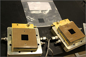Photo of a two gold metal boxes with a small black square in the middle.