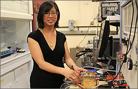 Photo of a woman, in a lab, holding a metal box with wires attached.