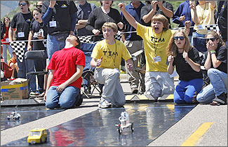 Photo of students crouched at the top of straight black rubberized race tracks reacting with both excitement and disappointment as their hydrogen-powered model cars begin a race. Behind them stand several adults who are coaching the student racing teams and serving as race judges.
