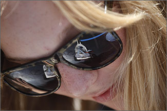 Photo of a student with blonde hair and freckles wearing black sunglasses. A reflection of a hydrogen fuel cell model race car waiting at the starting line on the race track is visible in the lenses of her sunglasses.