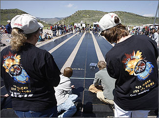 Photo of the finish line at a model solar race car competition. Long straight race tracks made of black rubberized material lies atop an asphalt parking lot. Spectators line the sides of the race tracks, while judges wearing black T-shirts stand at the end waiting for the model cars to arrive.