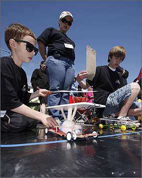 Photo of two boys kneeling under a bright blue sky to test their solar powered model race cars at the starting line of a black rubberized race track.