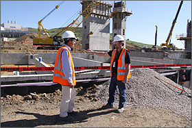Photo of two men standing in a construction area with concrete walls behind them.
