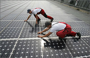 Photo of two men wearing red overalls installing solar panels on the flat roof of a warehouse in Germany.