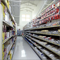 Photo of the inside of a retail store taken from ground level. Sunlight is illuminating rows of retail goods for sale.