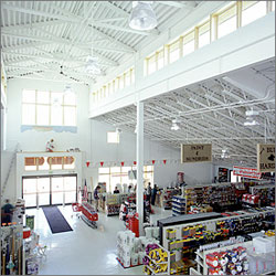 Photo of the inside of a retail store taken from up high. Sunlight is illuminating rows of retail goods for sale.