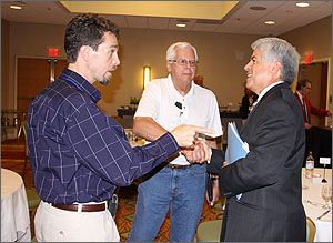 Photo of a man with a goatee pointing at a man dressed in a business suit as they discuss clean energy technologies. The man in the business suit is shaking hands with a third man wearing a white polo shirt.