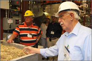 Photo of a man with white hair and a white moustache examines yellow-colored chips from corn plants in a large steel container. Behind him stands a man wearing an orange striped polo shirt.