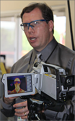 Photo of a man in a gray shirt and safety glasses speaking. In the foreground, the viewfinder of a video camera shows the thermal image of a man with the warmest areas of his body in red and orange.