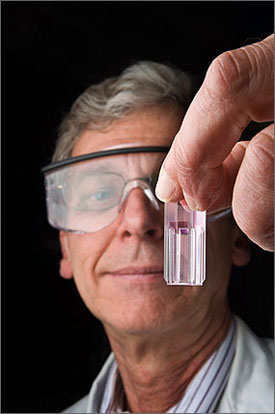 Photo of a man holding a test tube of a light purple liquid in front of his face. He is wearing safety glasses and spectacles.