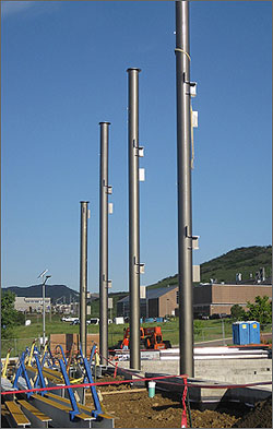 Photo of a line of four large metal tubes coming out of the ground in a construction site with blue sky, hills and buildings in the background.