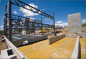 Photo of a construction site with concrete basement exposed steel with blue sky in the background.